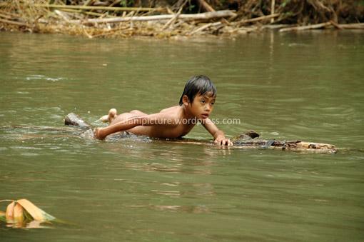 Tidak ada sampan, batang kayu pun bisa dipakai untuk bermain di sungai dalam.