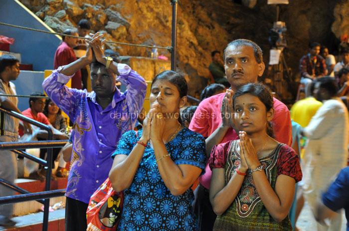 Keluarga pejiarah memanjatkan doa di depan kuil.