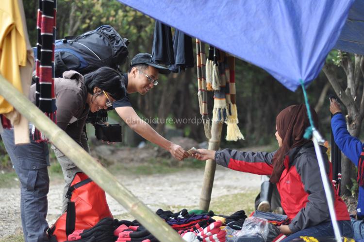 Dua pendaki sedang membeli masker dan syal  di area parkiran Gunung Papandayan.