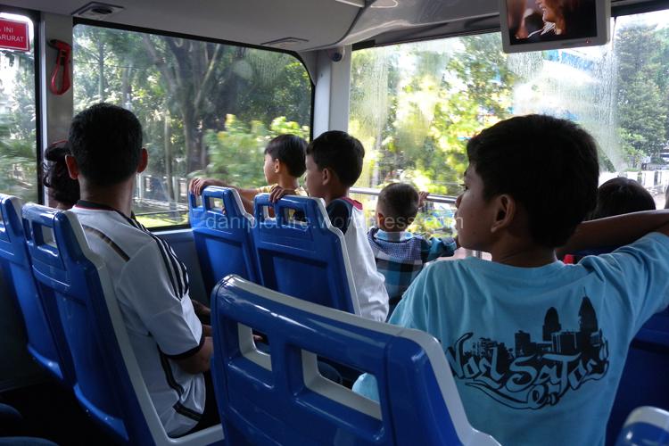Anak-anak sedang memperhatikan gedung yang sedang diceritakan sejarahnya oleh guide.